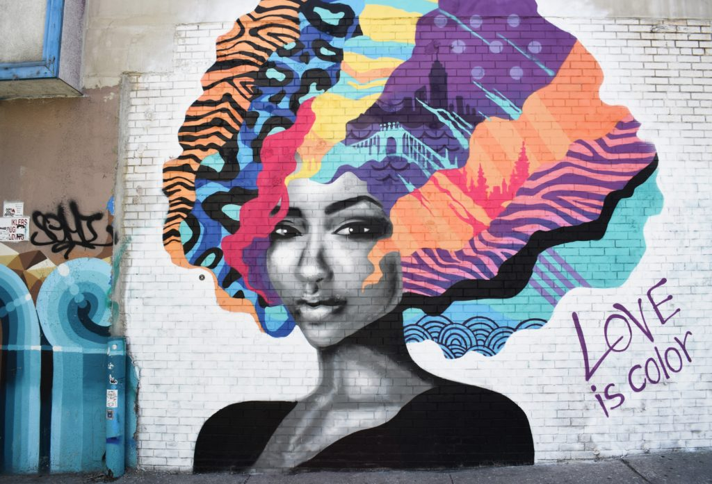 bright graffiti of a beautiful woman with multicolored hair and the slogan love is color