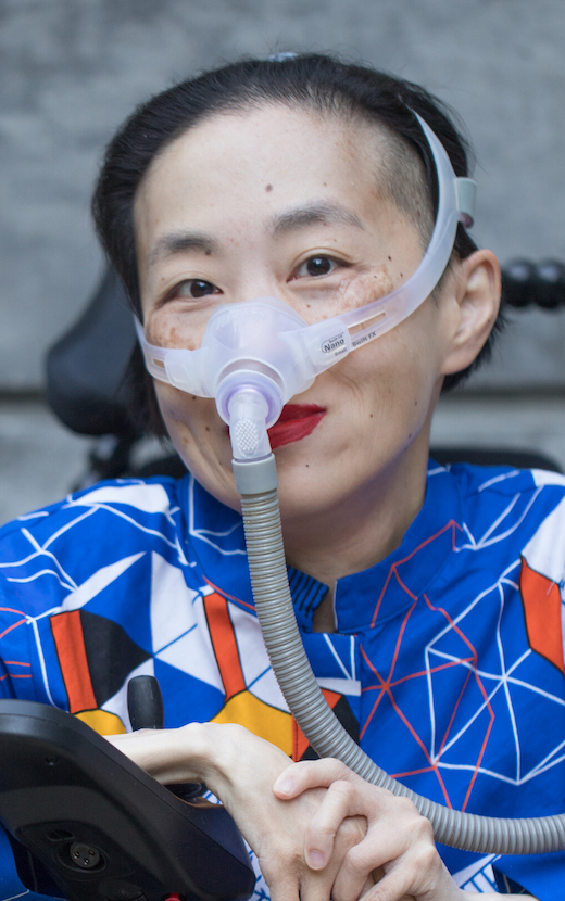 [Image Description: Photo of an Asian American woman in a power chair. She is wearing a blue shirt with a geometric pattern with orange, black, white, and yellow lines and cubes. She is wearing a mask over her nose attached to a gray tube and bright red lip color. She is smiling at the camera.] Photo Credit: Eddie Hernandez Photography