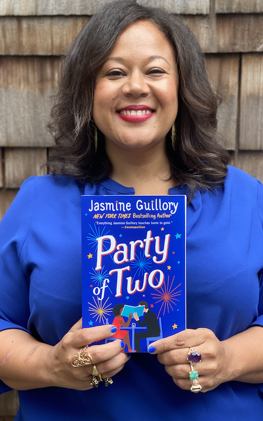 [Image Description: Photo of a Black woman smiling at the camera. She has shoulder-length brown hair, and is wearing red lipstick, large round gold earrings and a royal blue shirt. Her fingernail polish matches her shirt, and she is wearing rings on her fingers. In her hands she is holding up her novel Party of Two.] Photo Courtesy of Jasmine Guillory.