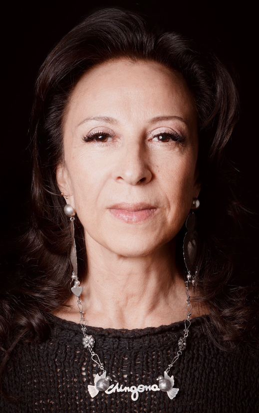 "Image Description: Photo of a Mexican American woman facing the camera. She has shoulder-length brown hair and wears long silver earrings and a silver chain necklace that says ""Chingona"" framed by two birds. The necklace rests on the front of her black sweater. Photo Credit: Kevin Abosch"
