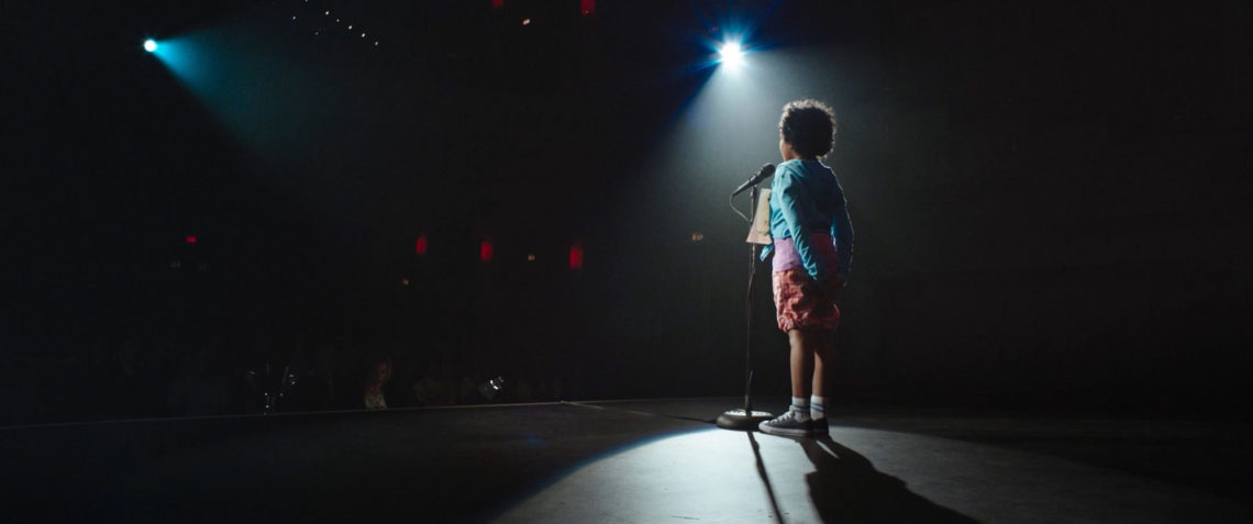 [Image Description: Photo of a child standing on a stage with a microphone in front of them and their hands clasped behind their back. They are standing beneath a spotlight with their back to the camera as they face the front of the stage. They have short, dark curly hair, and they are wearing a pale blue shirt, red shorts, and sneakers. The rest of the image is dark.] Photo Credit: June Street Productions