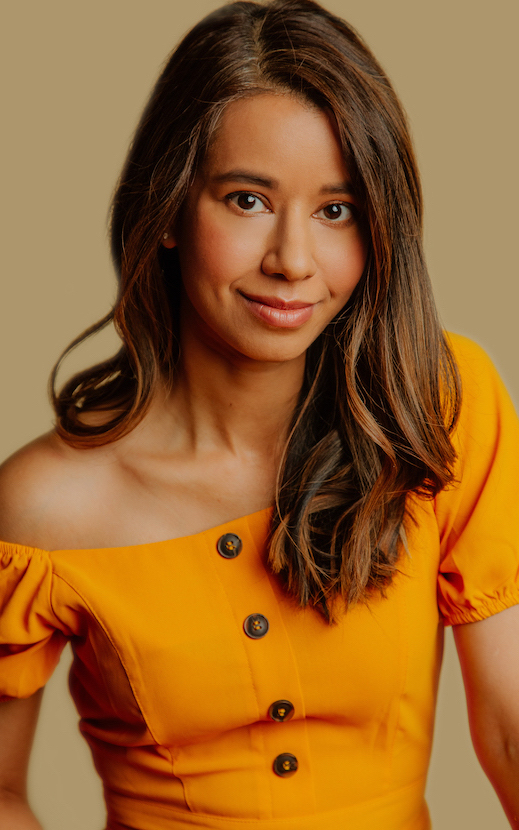 [Image Description: Photo of a South Asian American woman with shoulder-length dark brown hair with warm highlights. She is wearing an orange off-shoulder shirt and looking at the camera.] Photo Credit: Greggywawa Photography