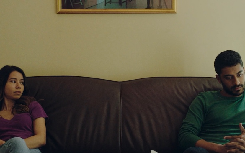 [Image Description: Photo of a South Asian American woman and a South Asian American man sitting on opposite ends of a couch. The woman has shoulder-length dark hair, and is wearing a purple t-shirt. She is looking over at the man sitting on the other side of the couch. The man wears a green long-sleeved shirt. He is looking down and his hands are clasped in his lap.] Photo Credit: June Street Productions