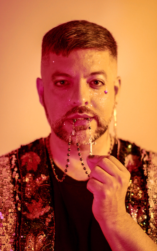 [Image Description: A peach-colored photo of a Latinx man looking directly into the camera, holding a rosary in his teeth. He has short brown hair and a brown and silver mustache and beard. He has glitter on his face and a pink rhinestone beneath his left eye. He wears a dangling gold earring in his left ear, and a glittering sequined vest over a black shirt.] Photo Credit: Marley Trigg Stewart
