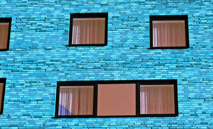 Bright blue brick building with many square windows